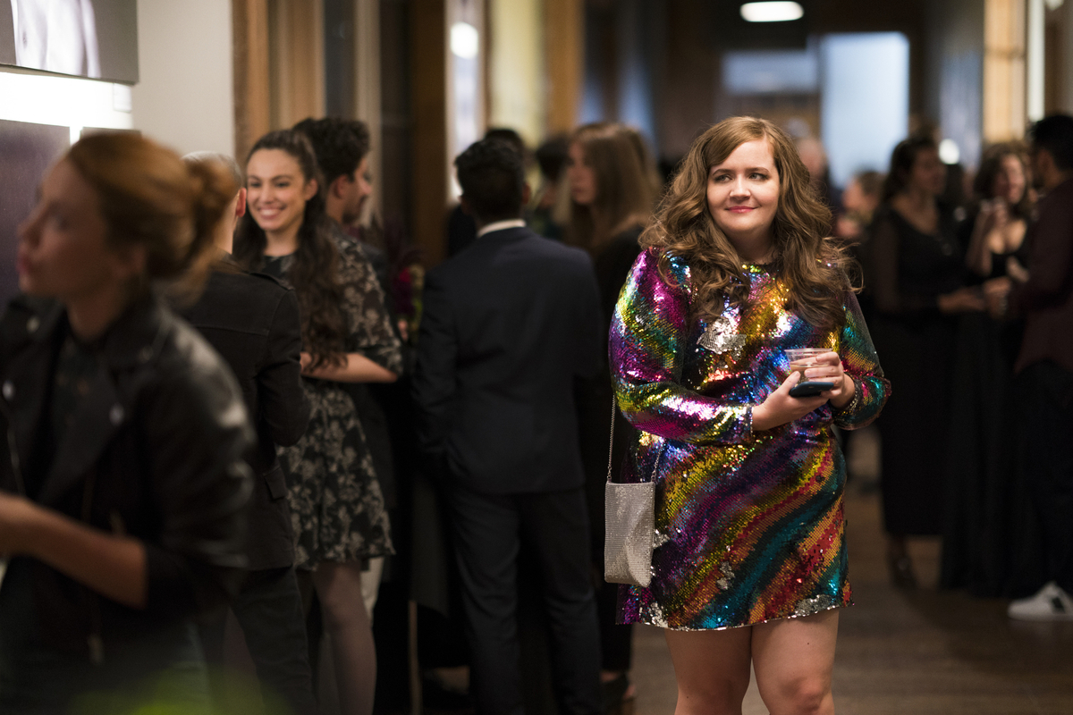 aidy bryant in a rainbow sequin dress walking through a crowd