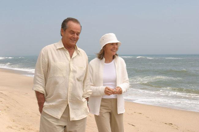 An elderly couple walks on the beach.