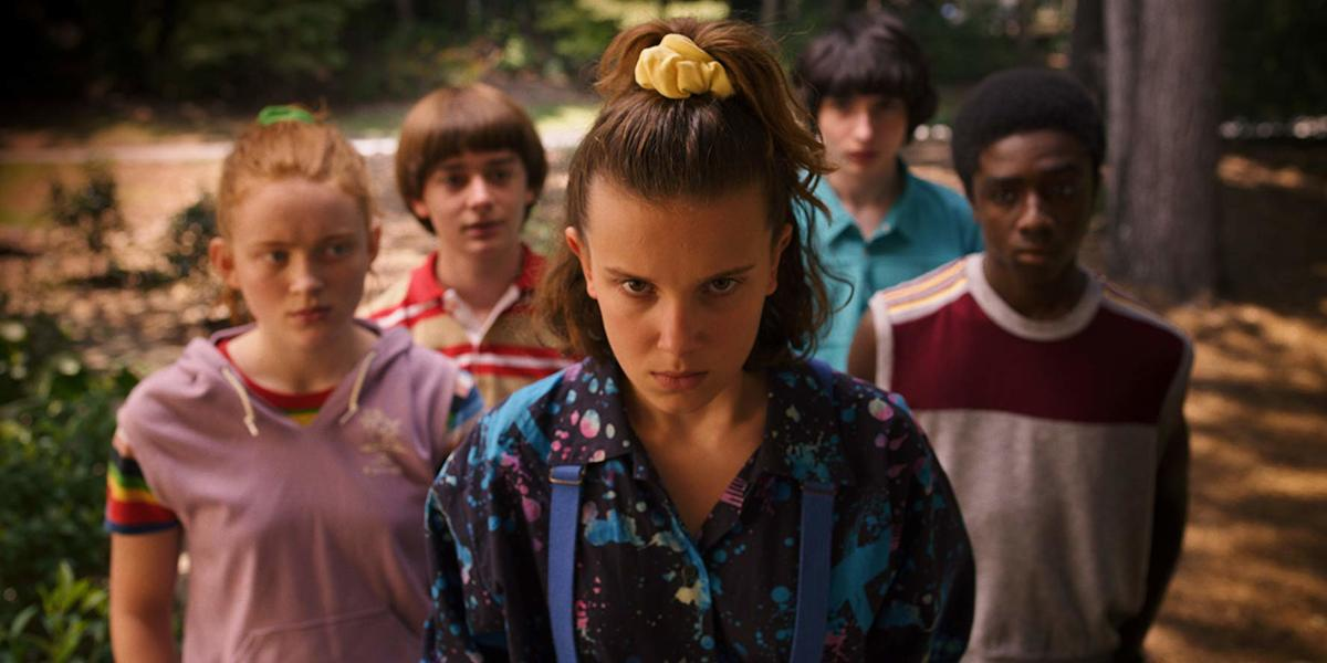 Caleb McLaughlin, Sadie Sink, Millie Bobby Brown, Finn Wolfhard, and Noah Schnapp in 80s clothes in a scene for stranger things