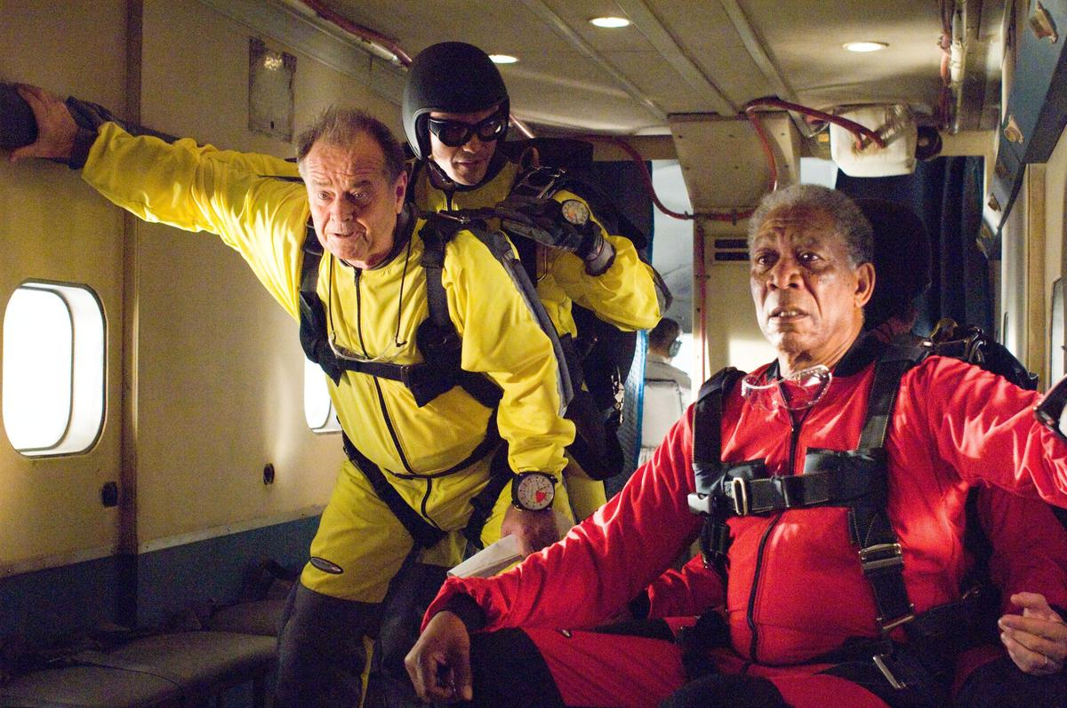 Two elderly men look worried while preparing to jump out of a plane.