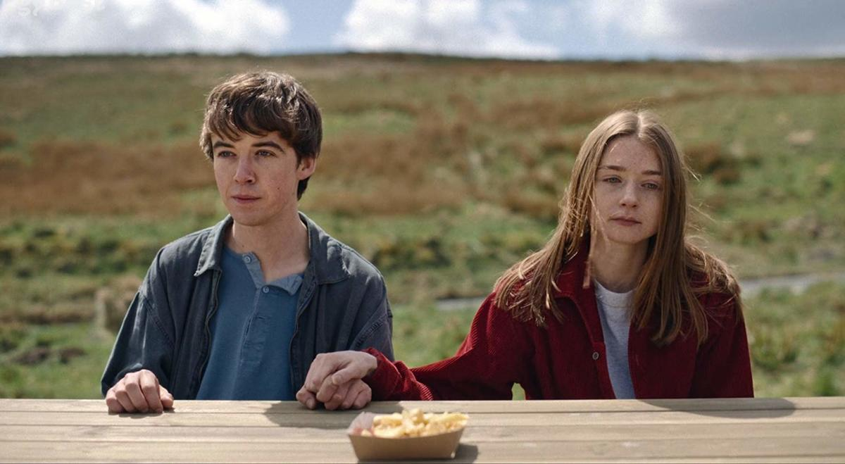 Jessica Barden and Alex Lawther holding hands outside at a picnic table