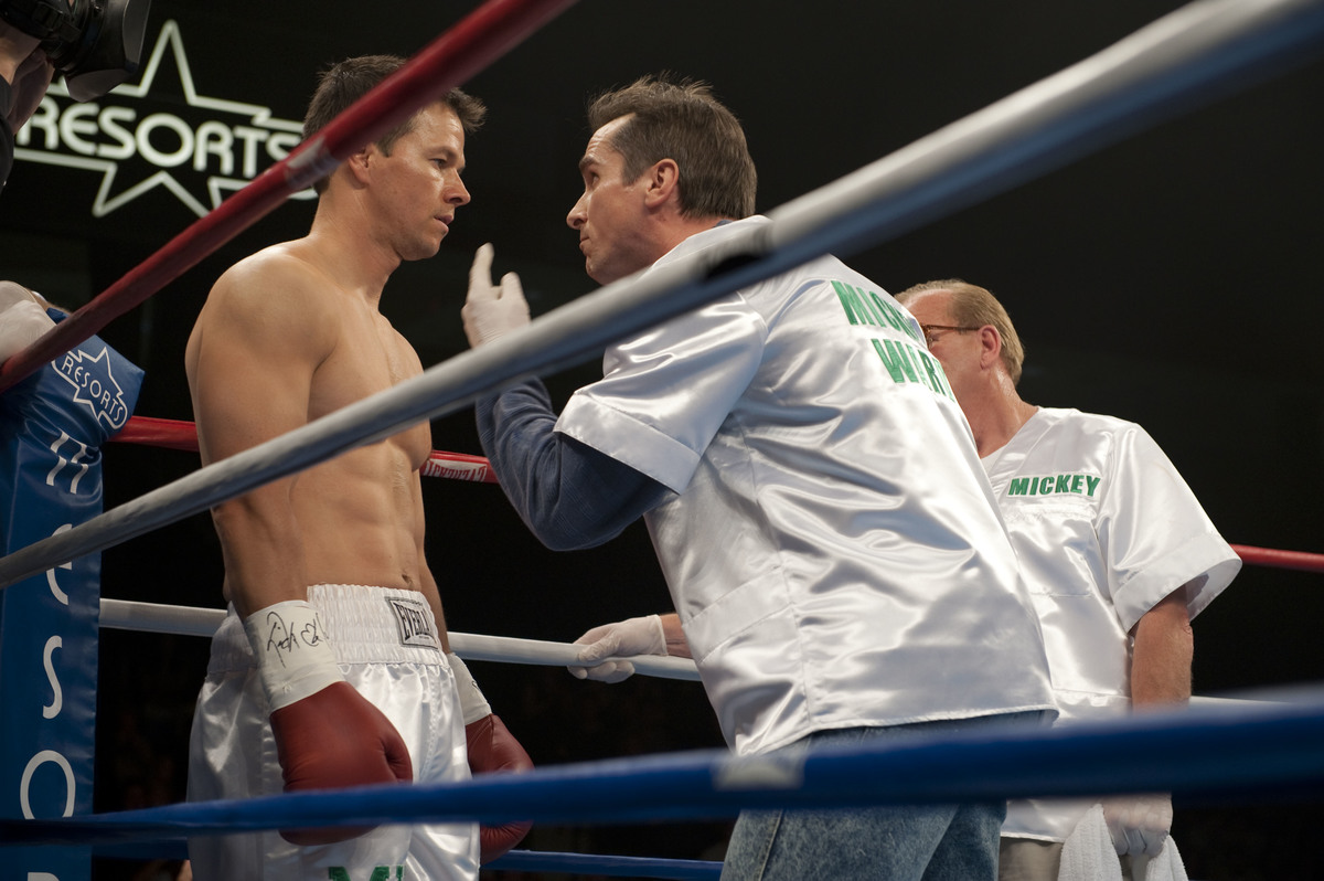 A boxing coach counsels his boxer in the ring.