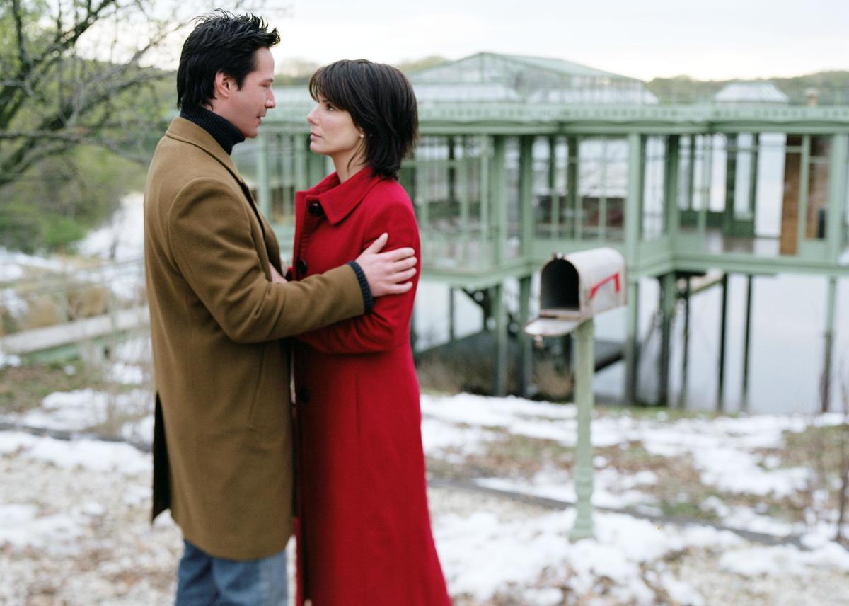 A couple looks at one another in front of a lake house.