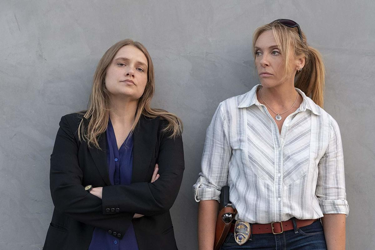 Toni Collette and Merritt Wever standing against a wall