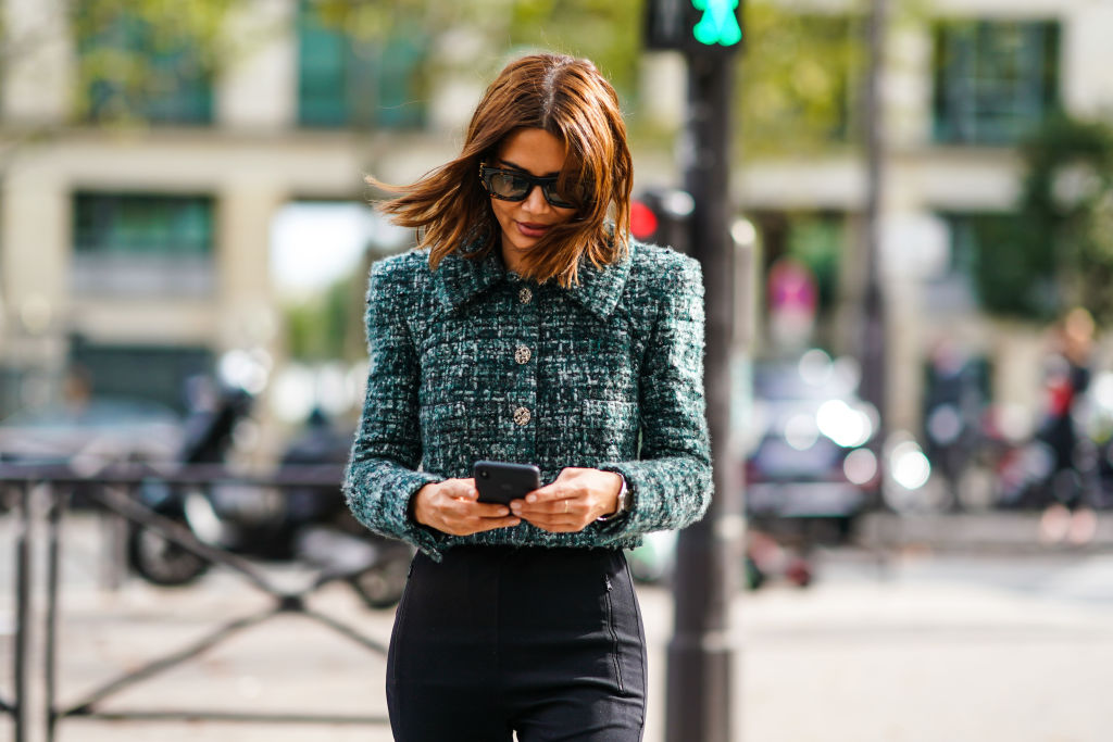 A woman smirks while she texts and walks down a street.