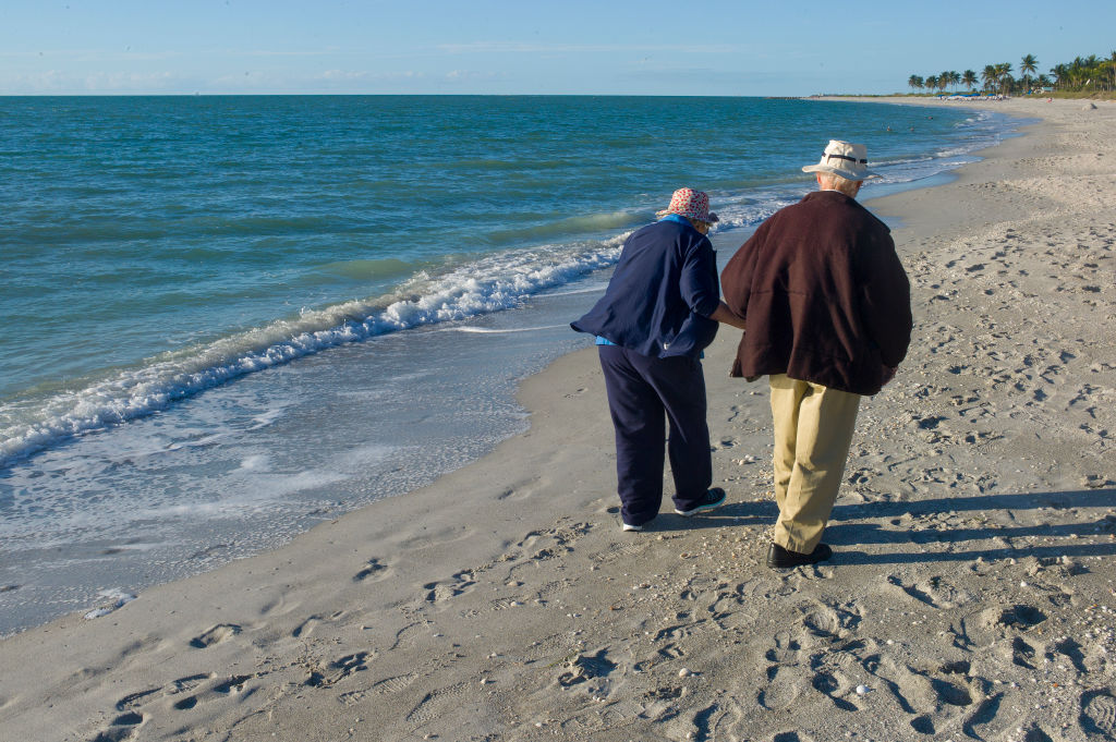 An elderly couple walks on the beach.
