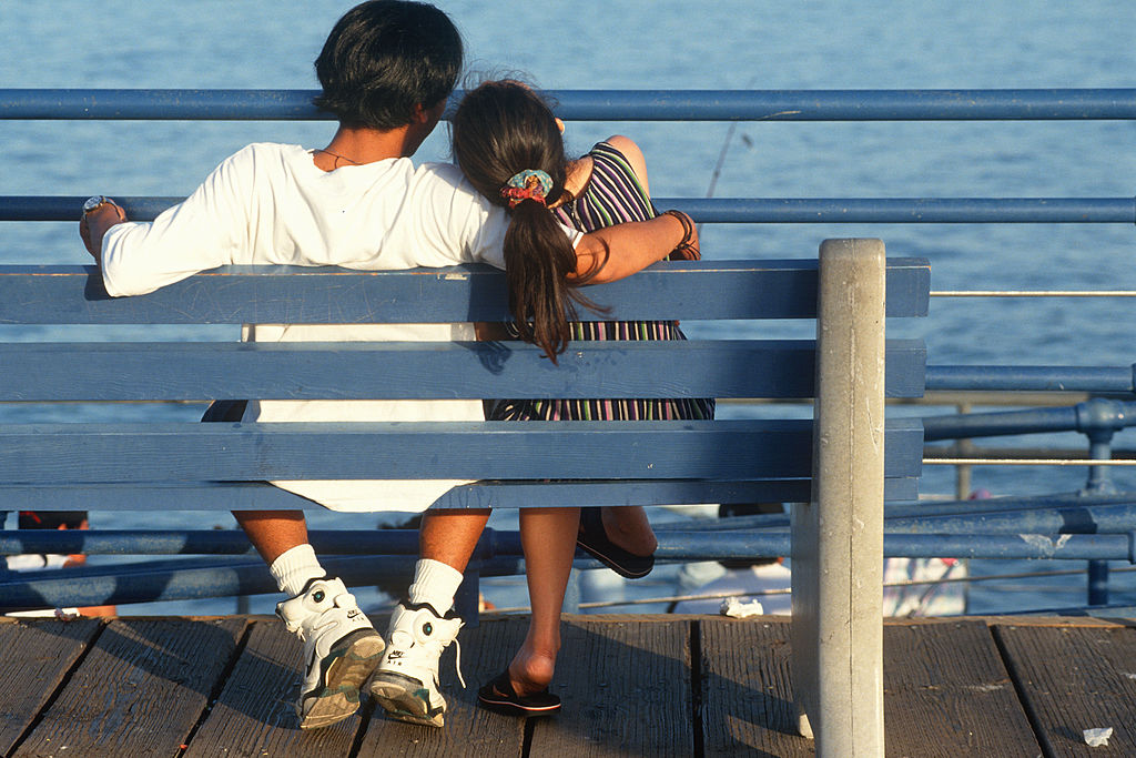 A couple sits on a bench on the pier.