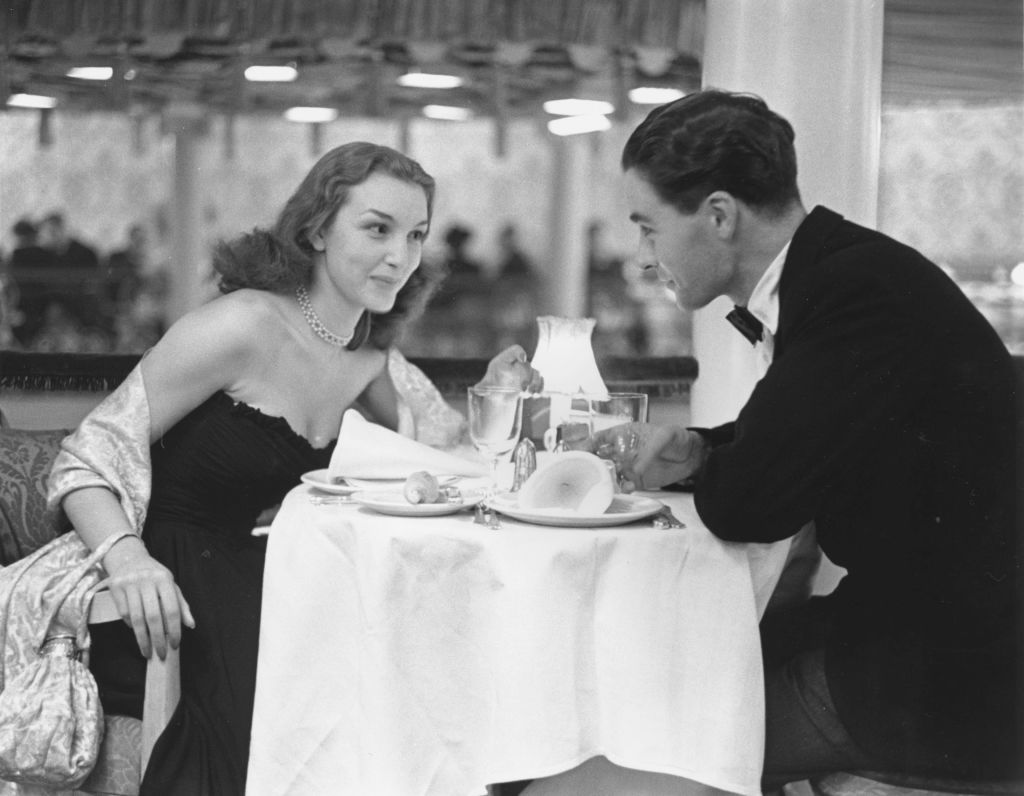 A man and woman look at one another over dinner at a restaurant.