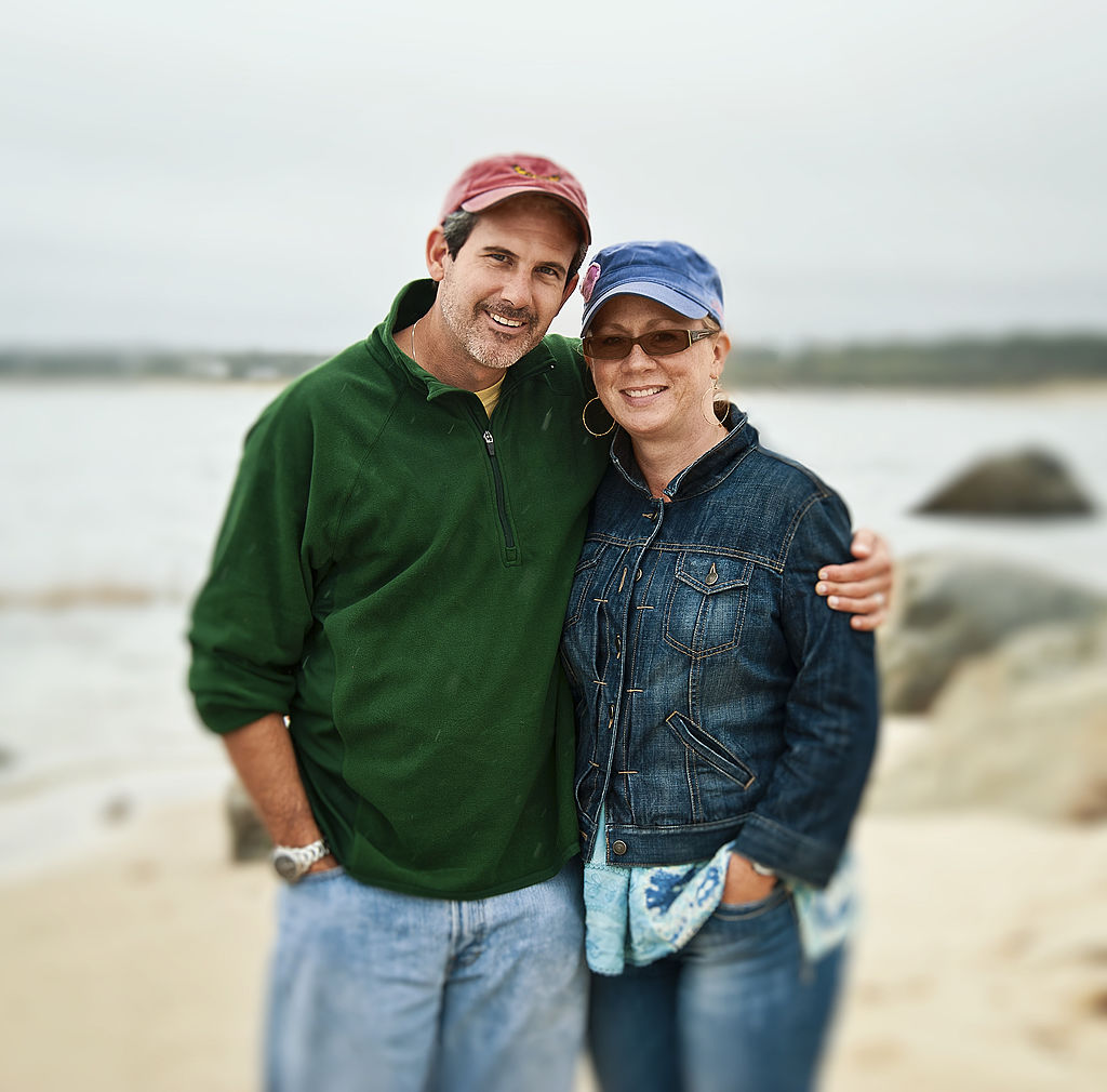 A middle-aged couple poses on the beach.