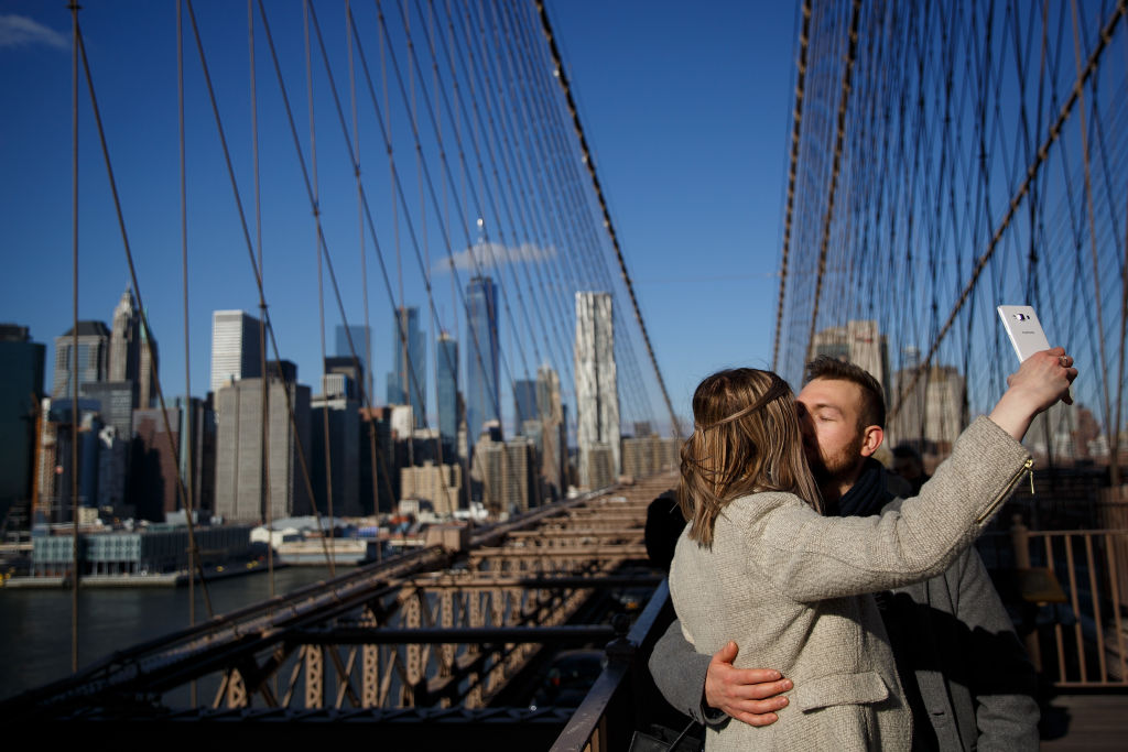 A woman takes a selfie of her and her boyfriend kissing on a bridge.