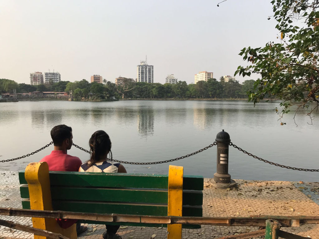 A couple sits on a bench overlooking a lake.