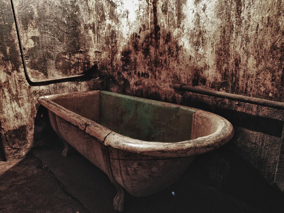 A dirty bathtub is seen in Australia's abandoned J Ward.