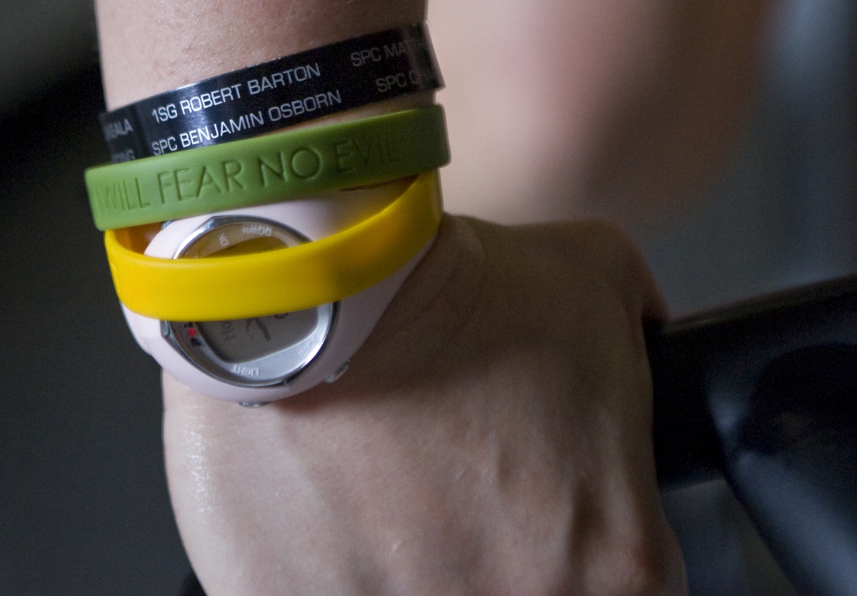 A woman wears rubber bracelets over a watch.