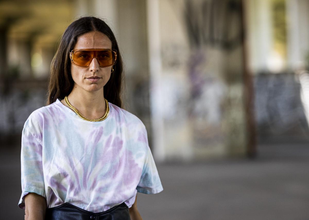 A woman wears a tie dye t-shirt.