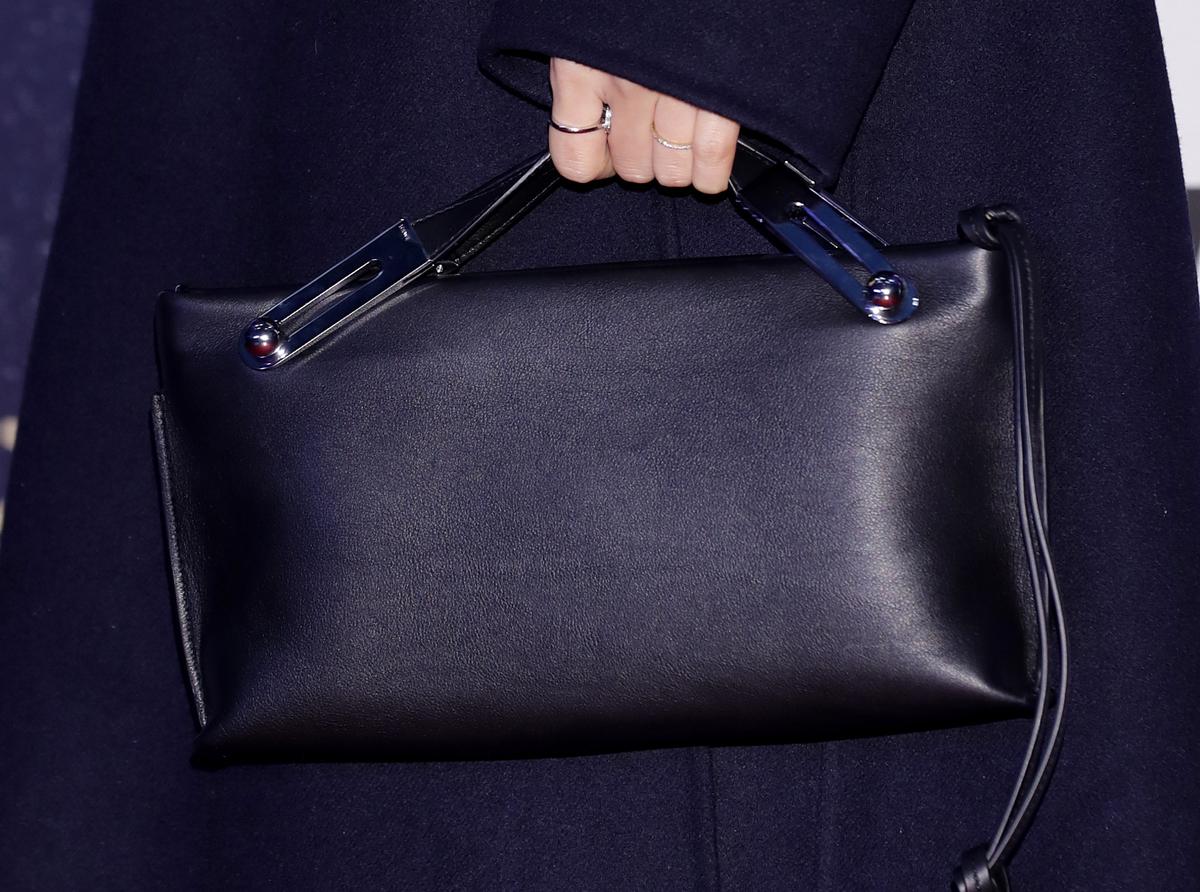 A woman holds a plain black rectangular purse.