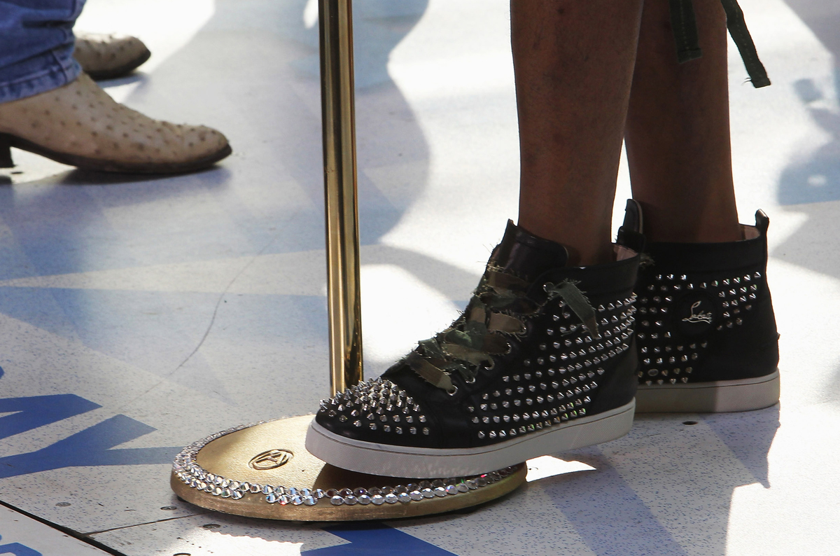 A person with bedazzled shoes steps on a microphone stand.
