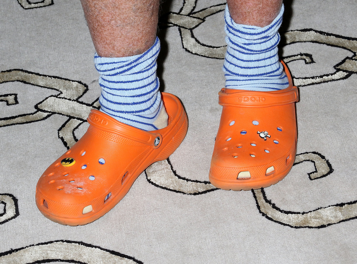 A man wears orange crocs with skull and Batman decorations.