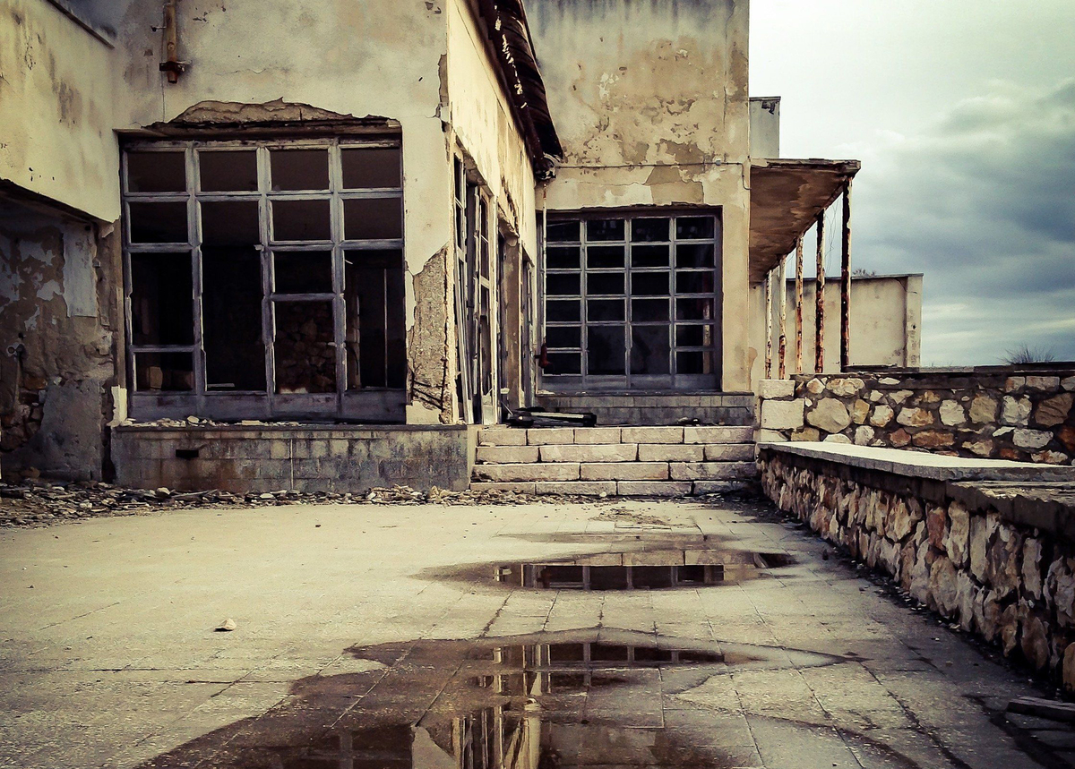 A puddle is outside the abandoned buildings of Goli Otok Prison.