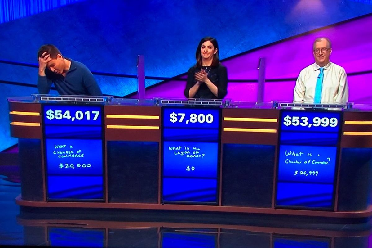 Contestants stand at their podiums as they play Jeopardy!