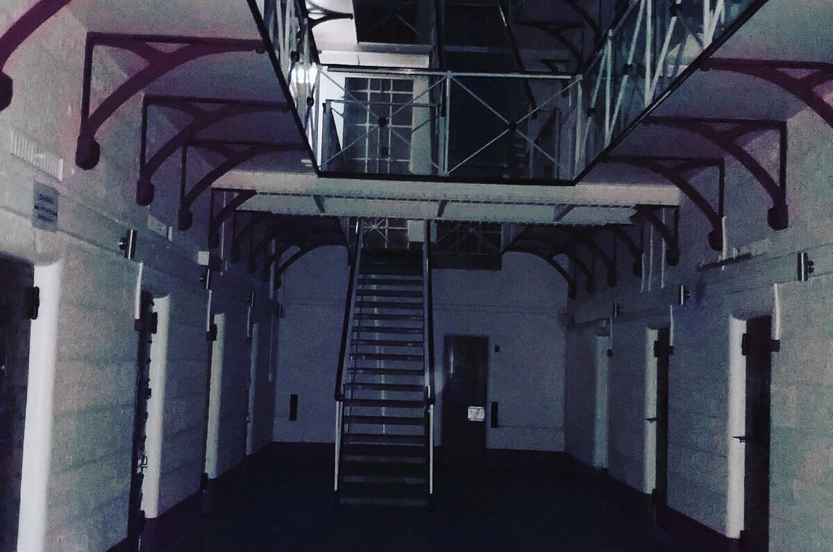 A photograph shows a staircase and cells in Pentridge Prison in Melbourne, Australia.