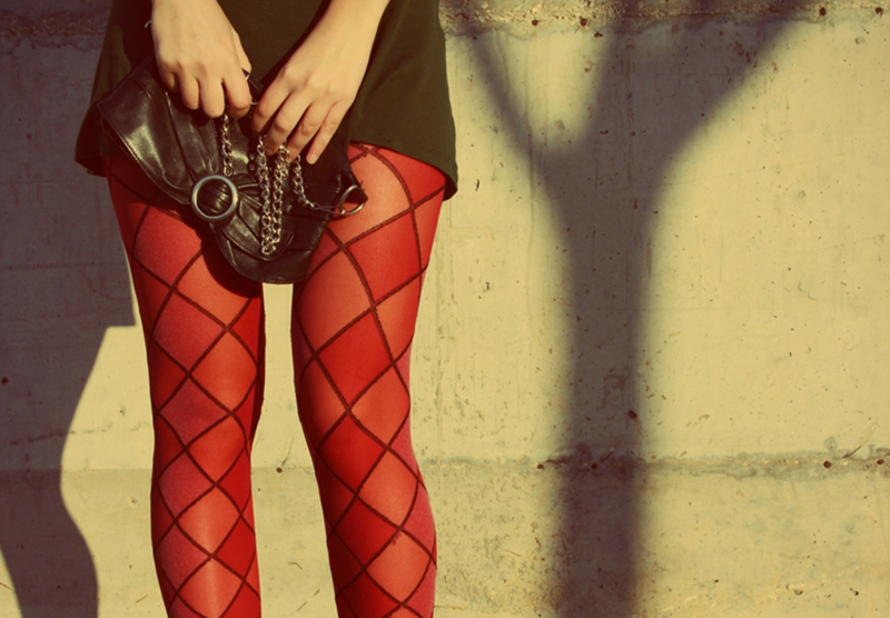 A woman wears red tights with a diamond pattern.