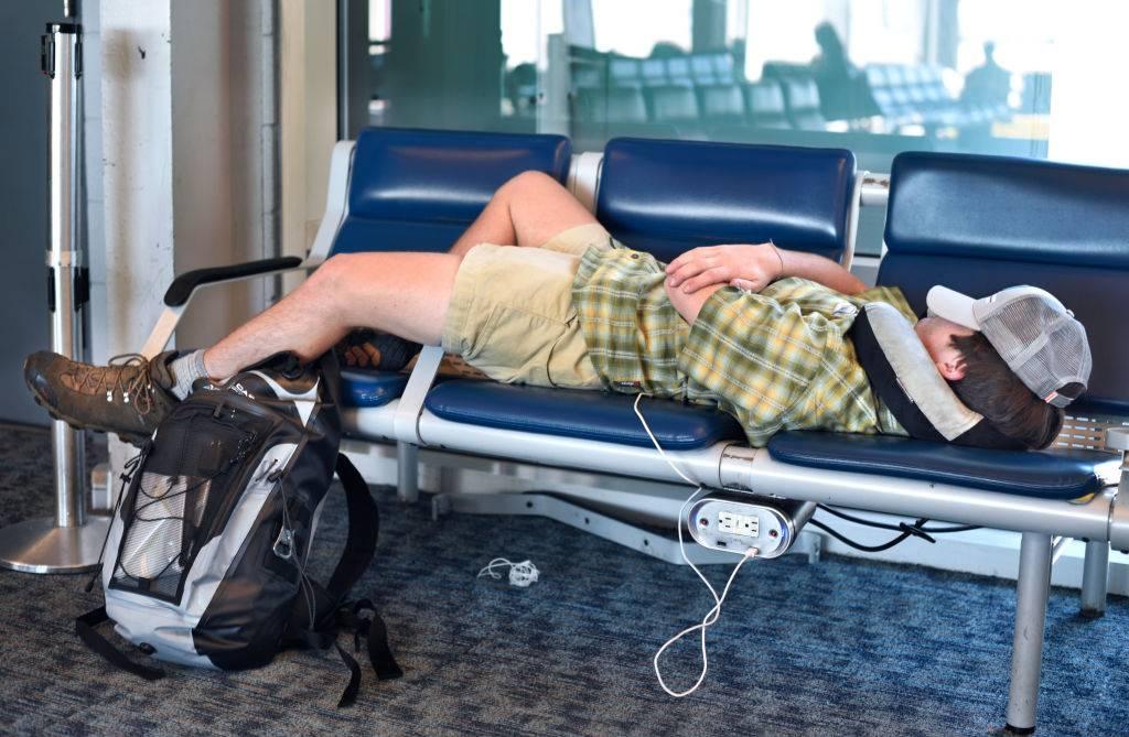 An airline passenger sleeps on terminal seats