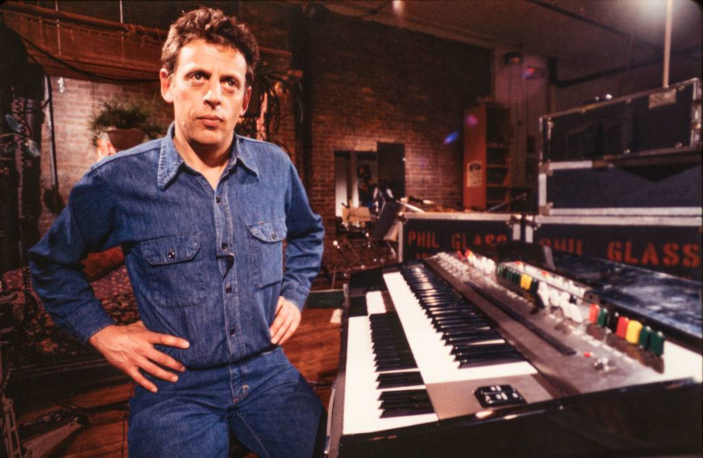 Portrait of American Minimalist composer and musician Philip Glass as he sits at a keyboard