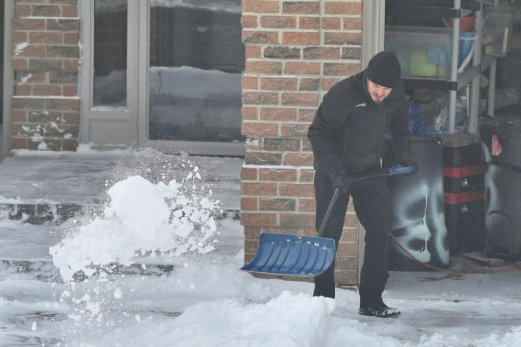 Man shovels snow from his driveway