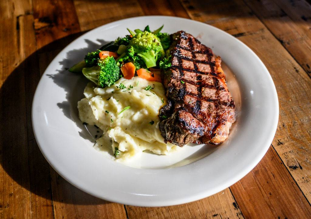Photo of a plate of grilled shell steak with mashed potatoes and sauteed vegetables