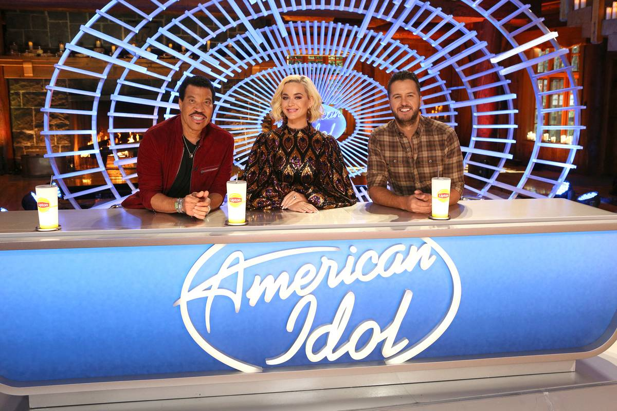 lionel richie, katy perry, and luke bryan sitting at the judges table for american idol