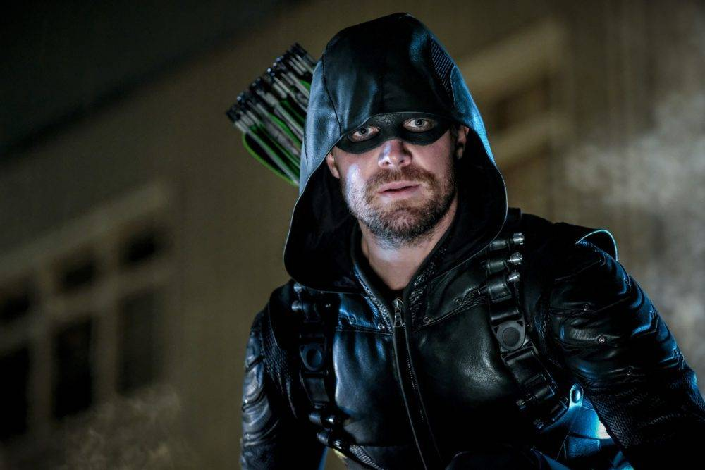 stephen amell wearing a leather jacket and black mask with arrows strapped to his back in arrow