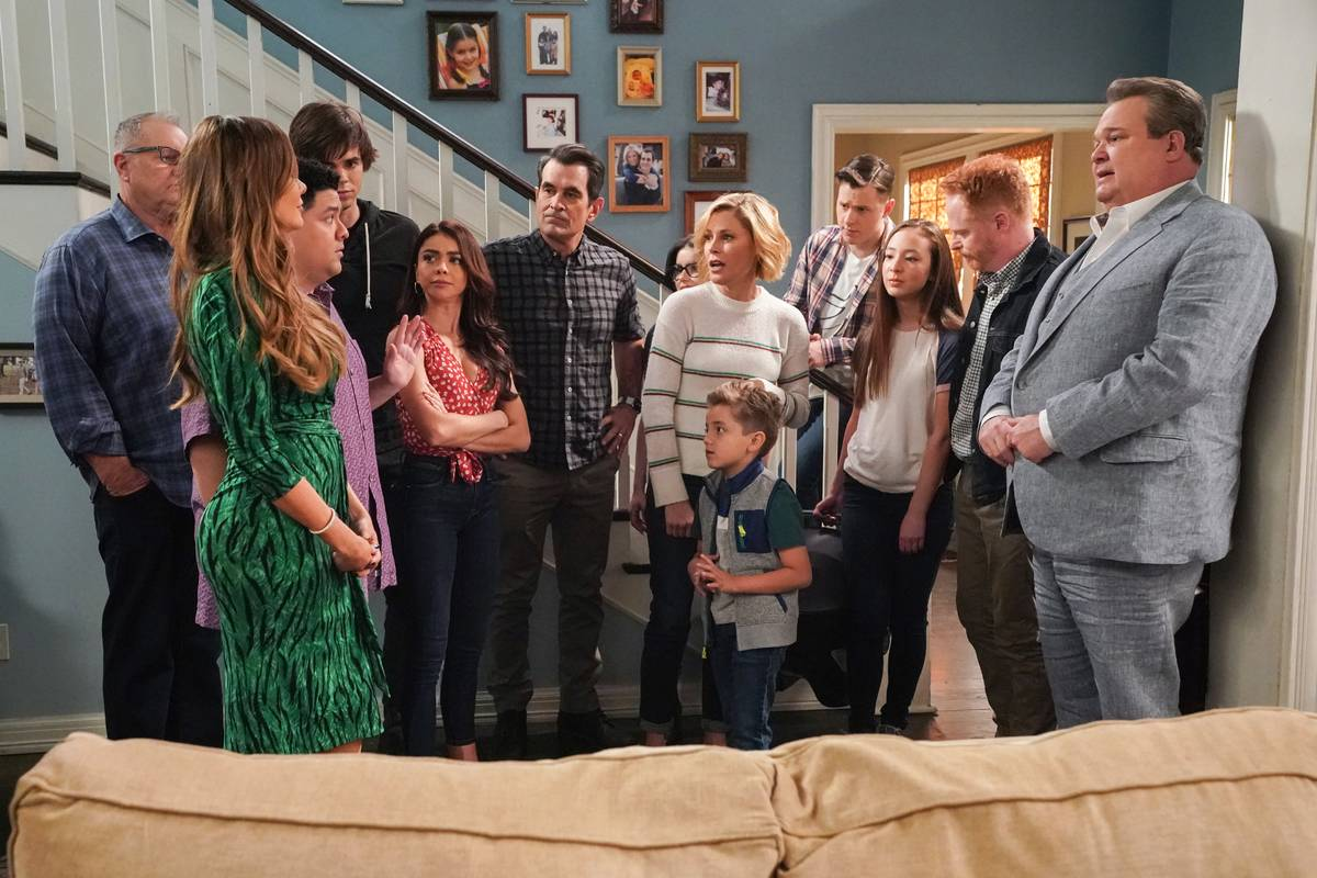 the cast of modern family standing together in a living room