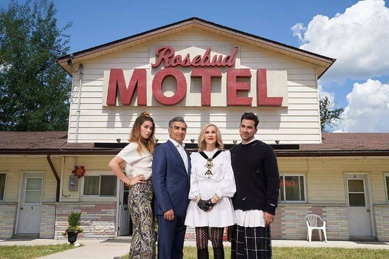 the cast of schitt's creek in front of the rosebud motel sign