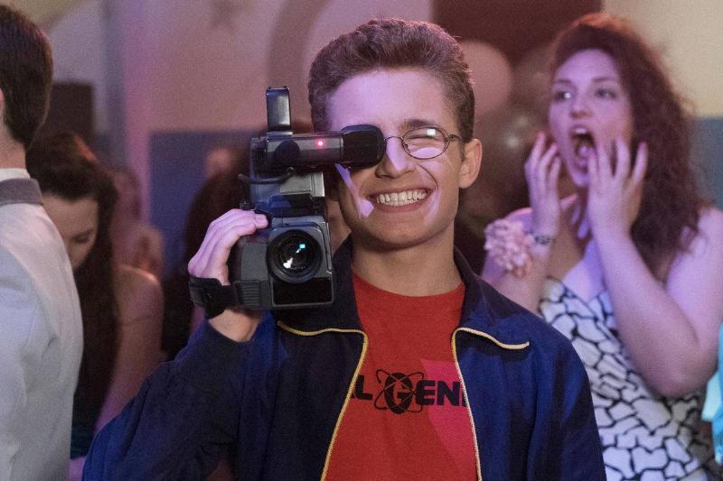 a boy holding up a retro camcorder