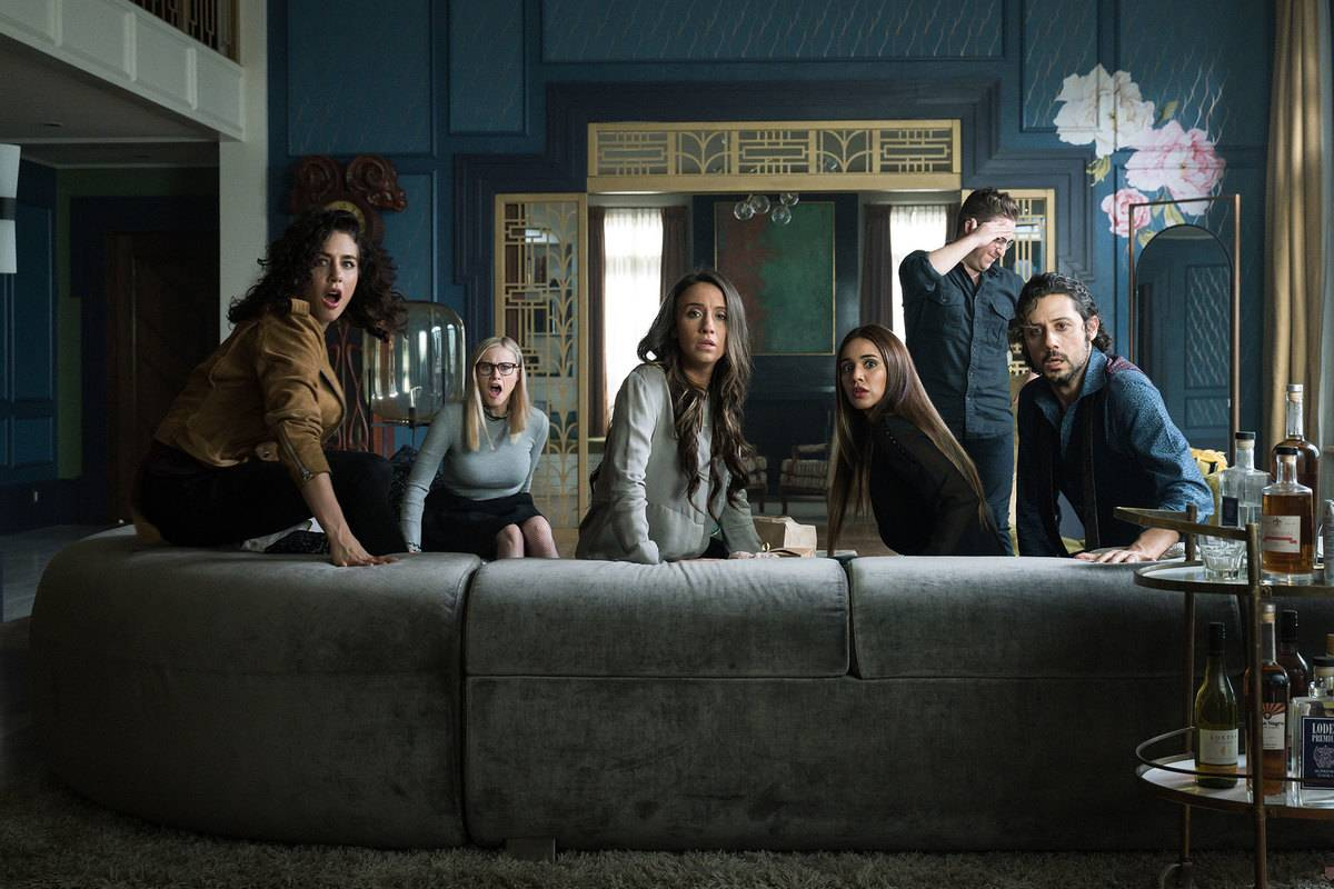 the cast of the magicians looking behind a couch