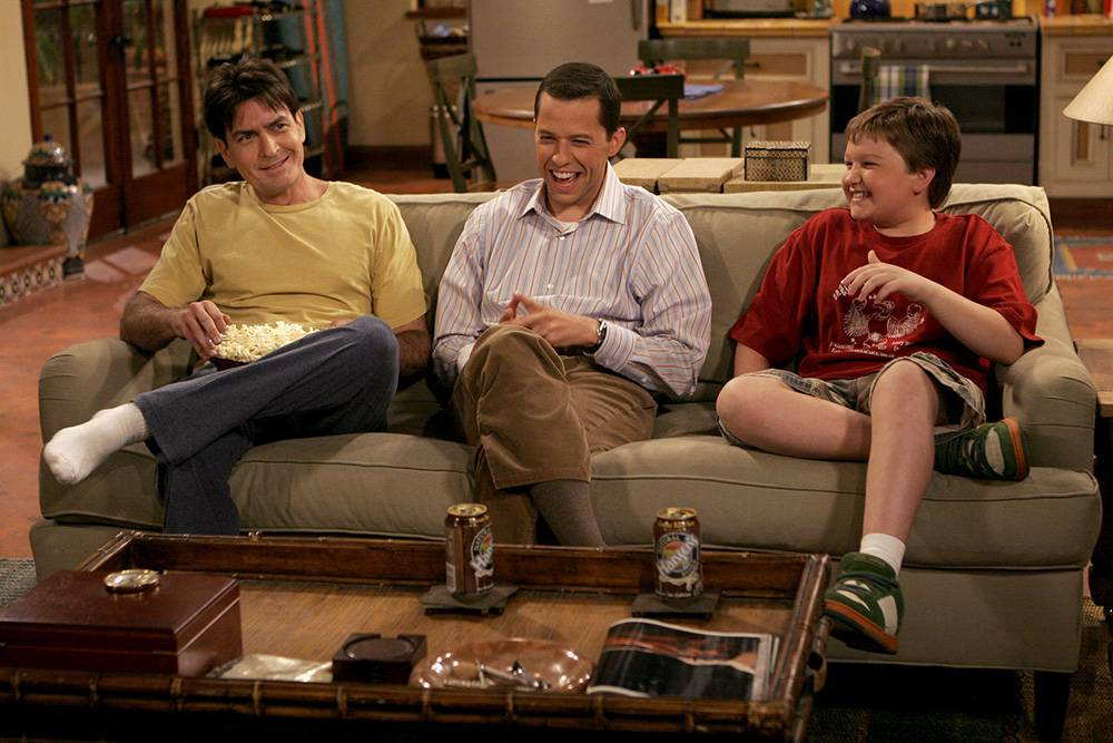 charlie sheen, angus t jones, and jon cryer sitting on a couch laughing