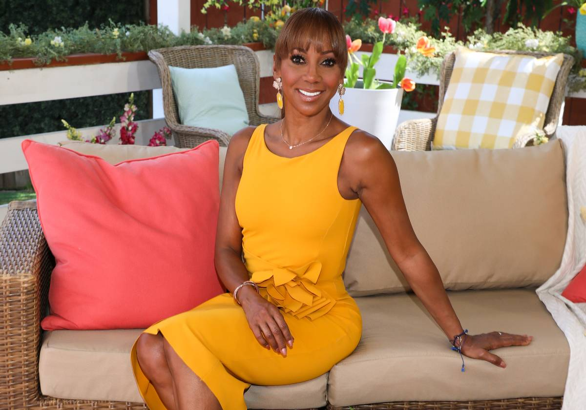 Actress Holly Robinson Peete sits on a couch at Hallmark's