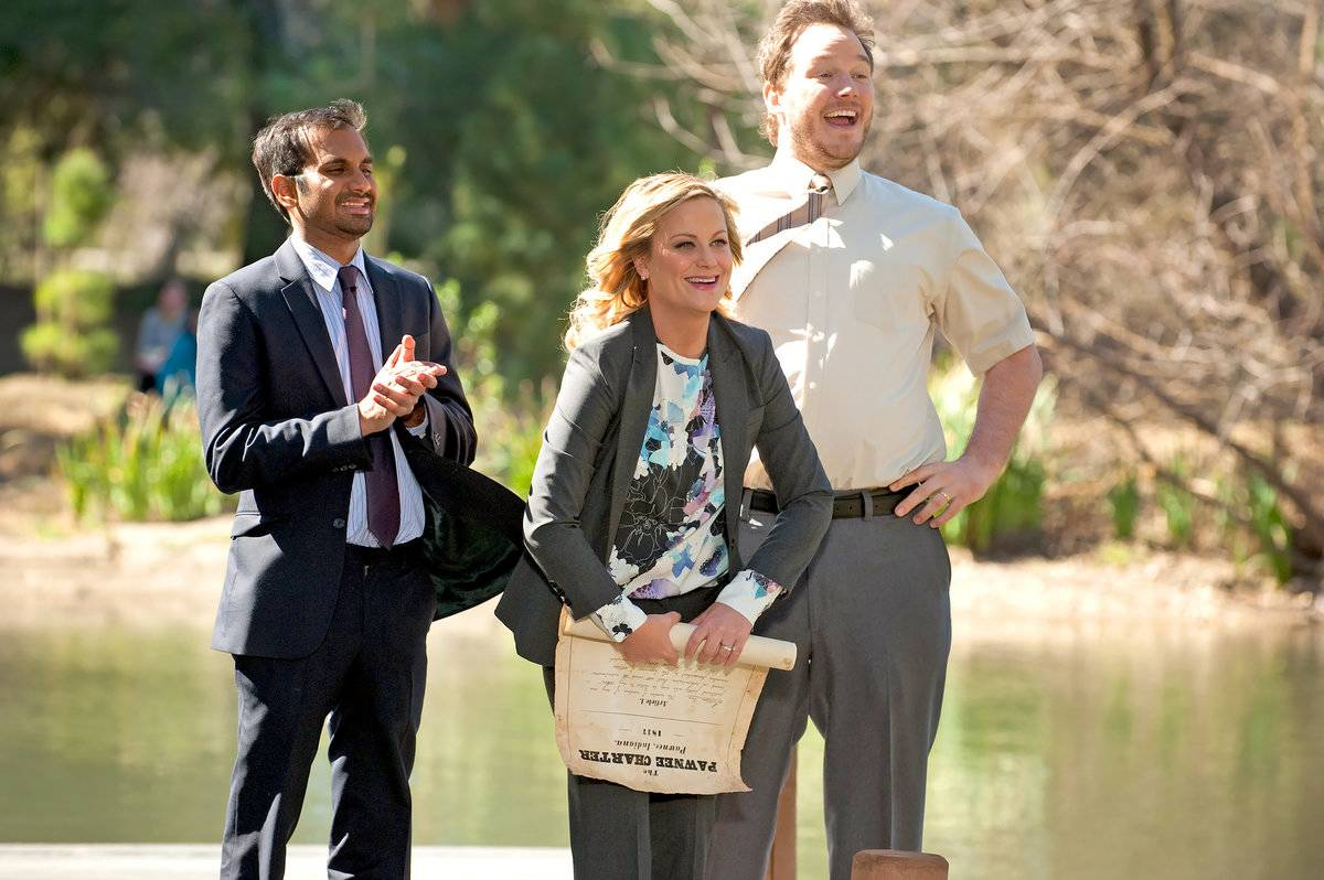 aziz ansari, amy poehler, and chris pratt standing in front of a lake