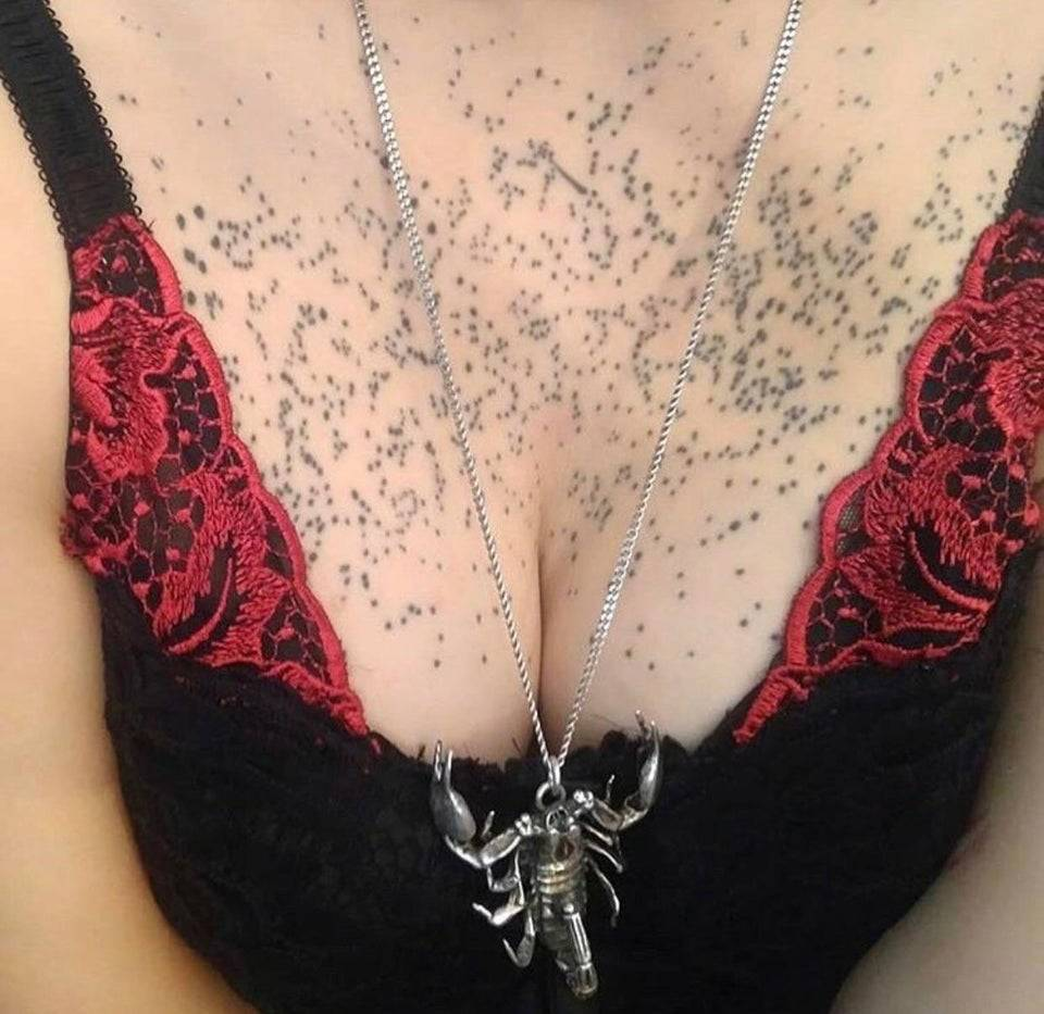 woman with chest tattoo that was meant to look like stars