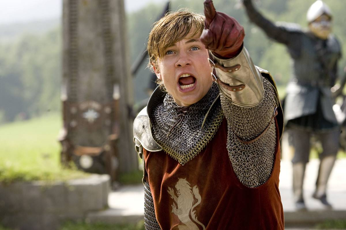 william moseley wearing a knight's uniform and pointing at something