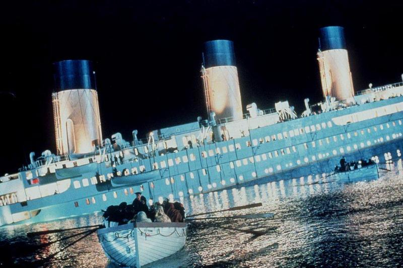 the titanic ship with passengers leaving on a small boat