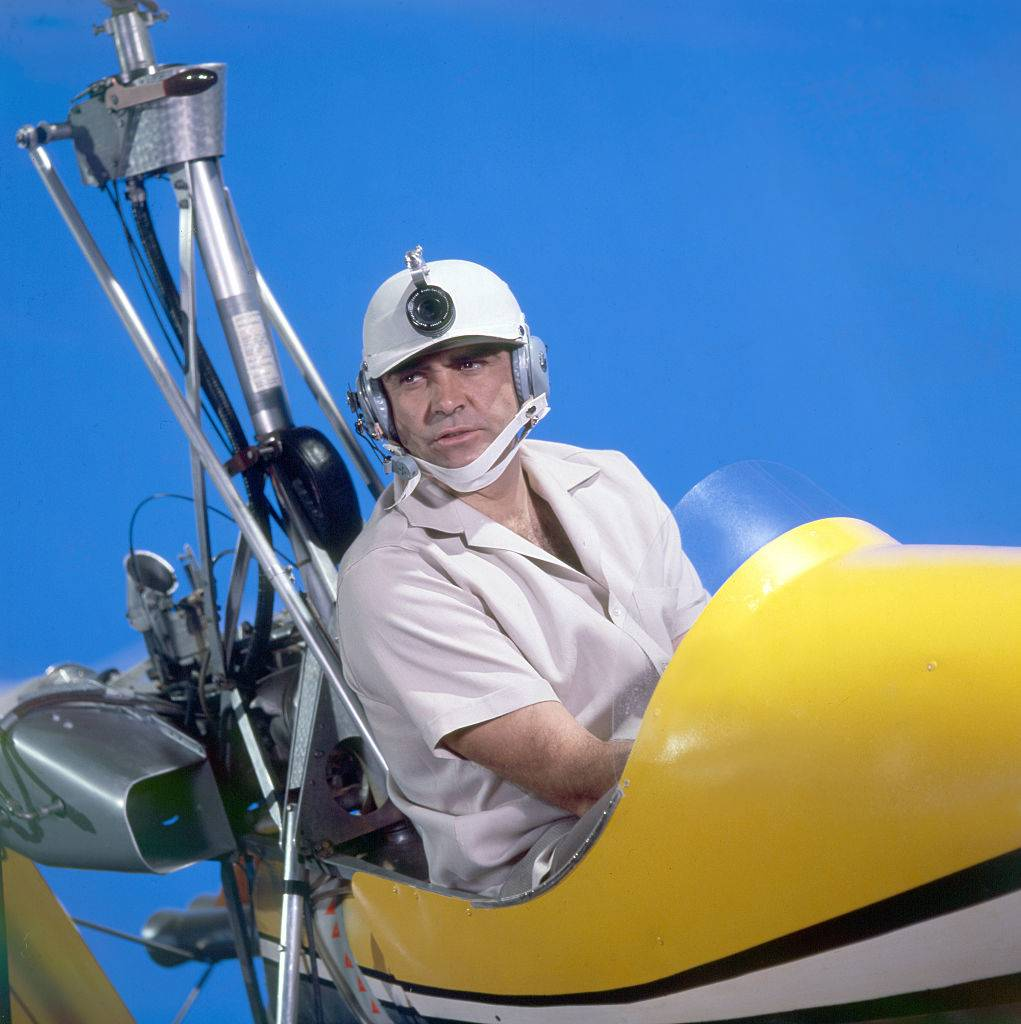 Sean Connery riding in a yellow airplane