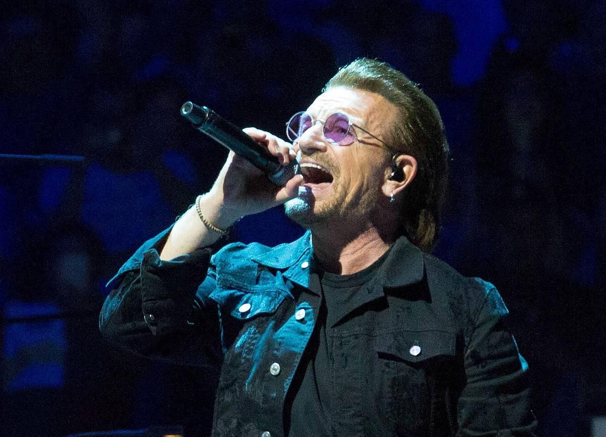 Bono sings onstage at a U2 concert.