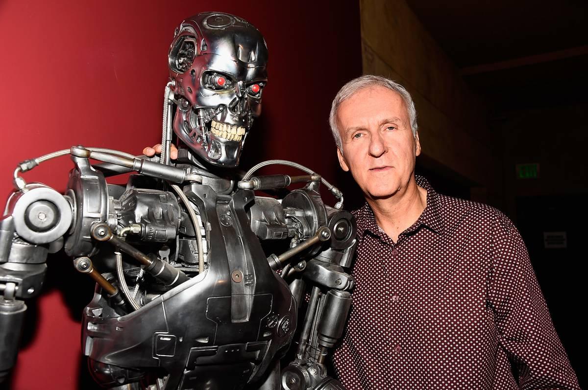 James Cameron stands next to a Terminator sculpture.