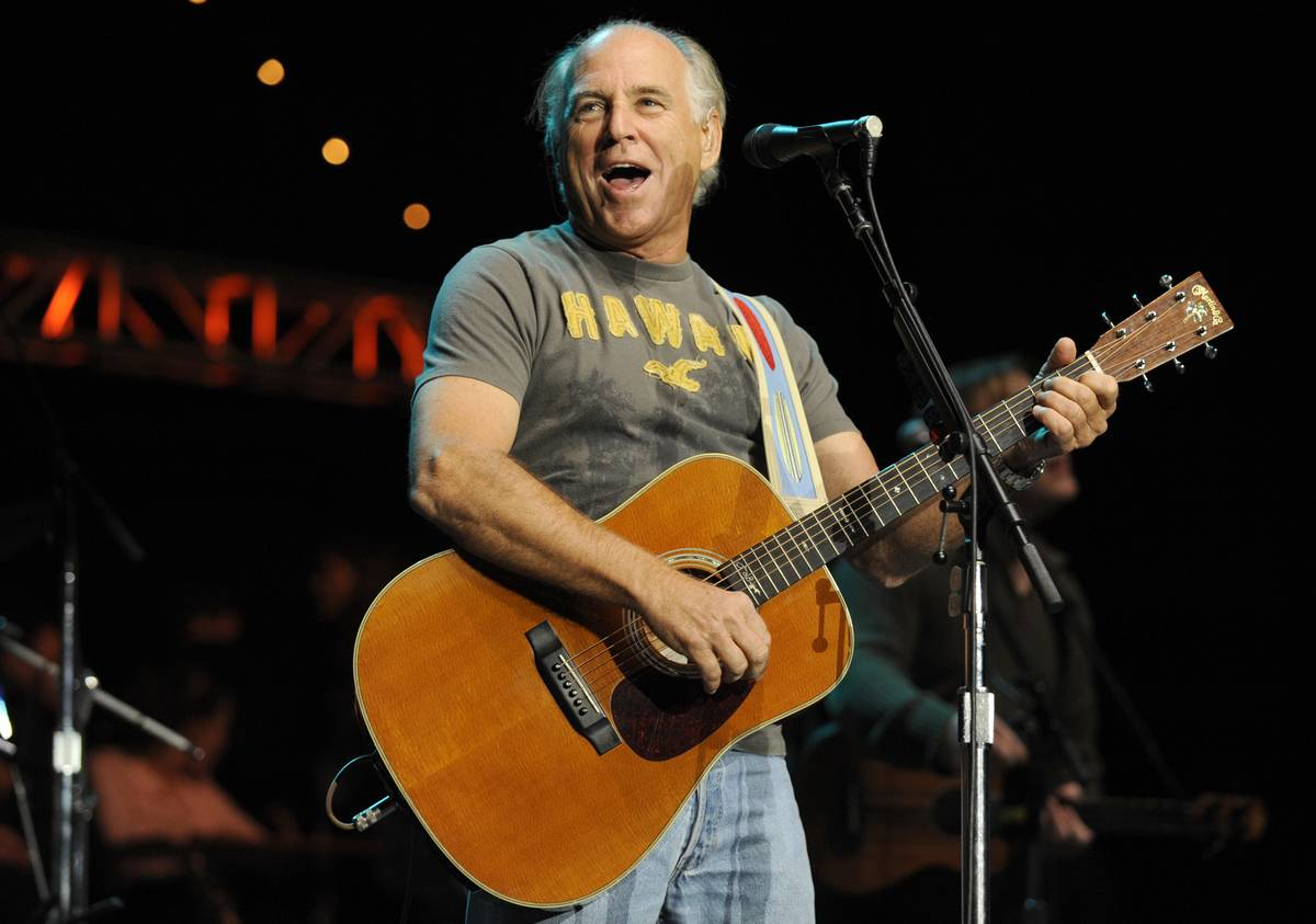 Jimmy Buffett sings and plays guitar while on stage.