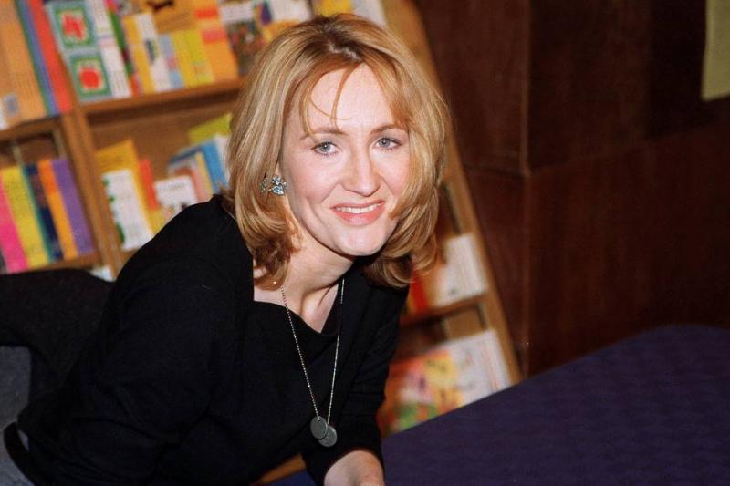 JK Rowling sits at a table ready to sign copies of her book.