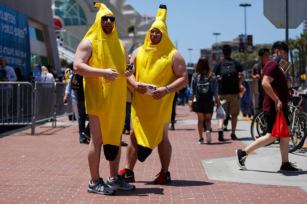 Attendees dressed in banana costumes stand outside the convention