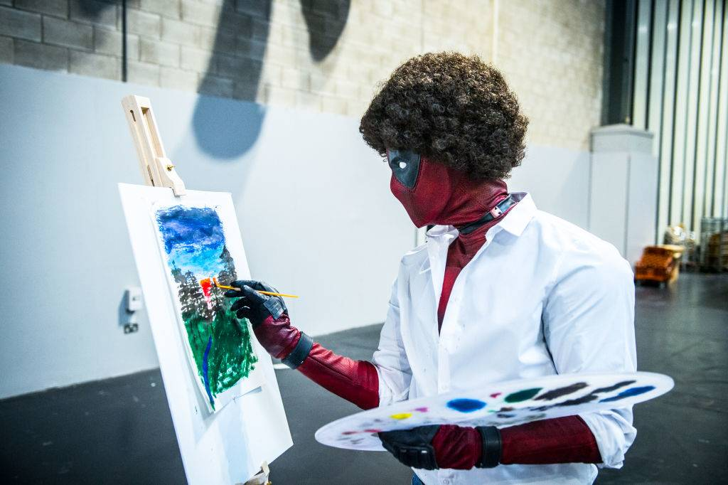 A Bob Ross Deadpool cosplayer painting in character