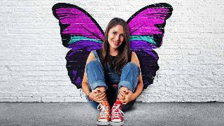 Soleil Moon Frye sitting against a wall with butterfly wings in punky brewster