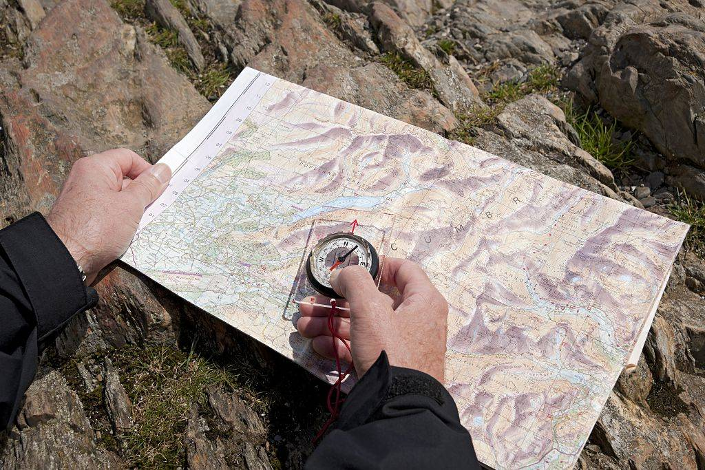 someone holding a compass and a map